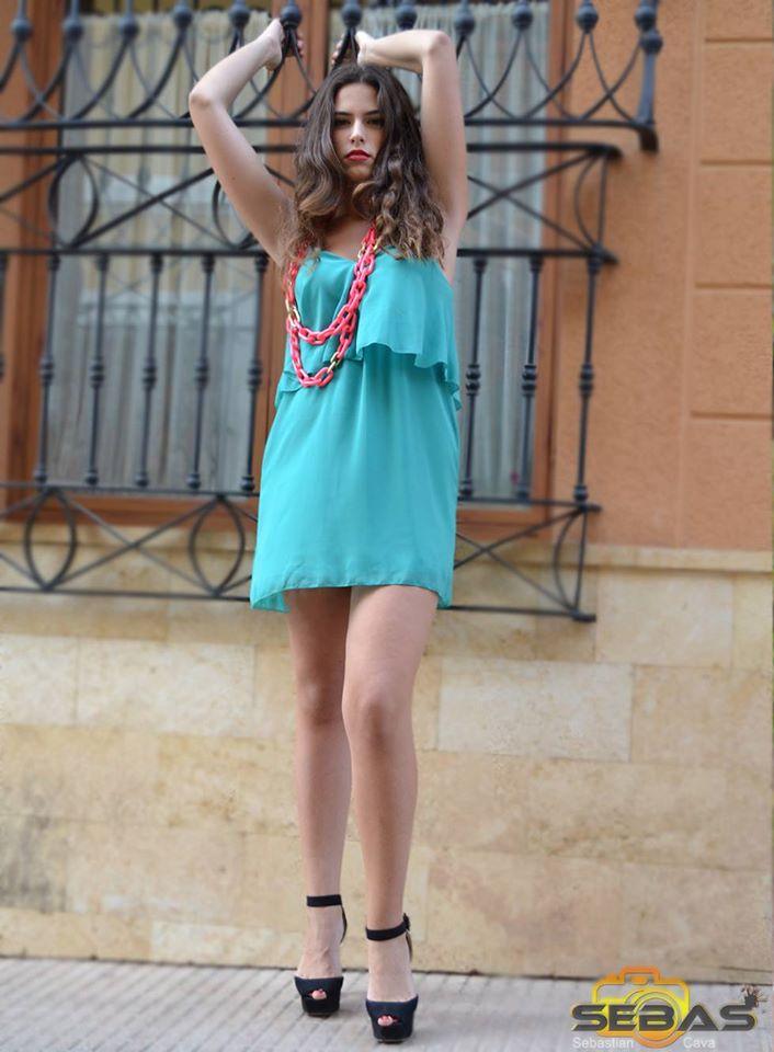 Modelo posando en ventana con vestido verde azulón y collar rosa