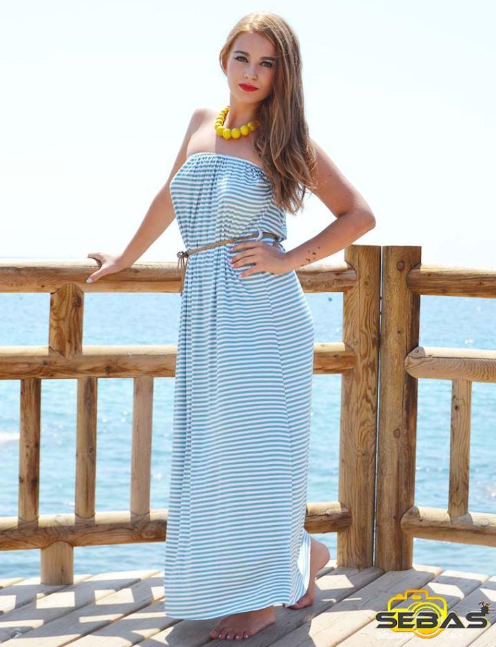 Modelo con vestido azul con rayas blancas, posando en la playa
