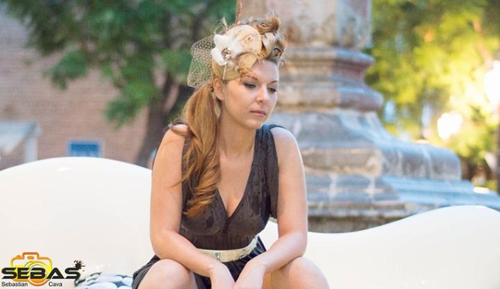 fotos de moda con modelo con vestido negro y tocado dorado y flor blanca
