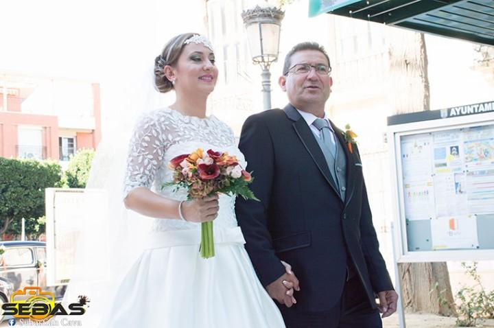 Novia y padre camino de la iglesia tres Avemarías con ramo de novia floristería Juani