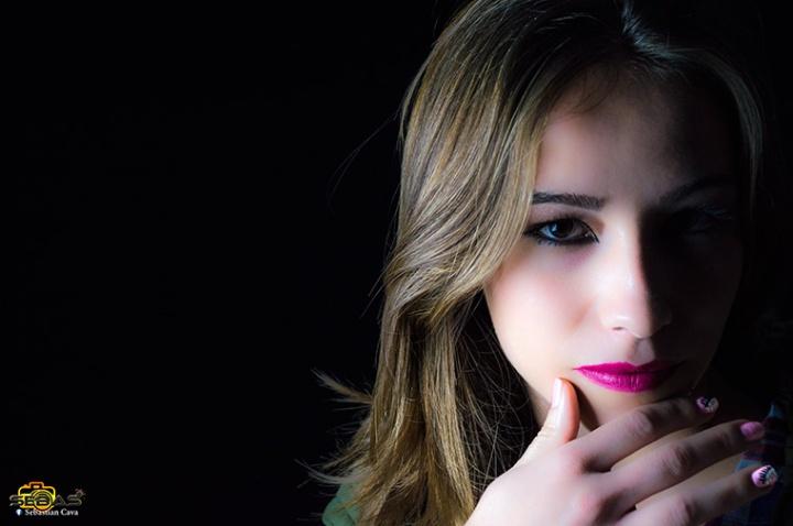 Chica maquillada con sombra en media cara y fondo blanco
