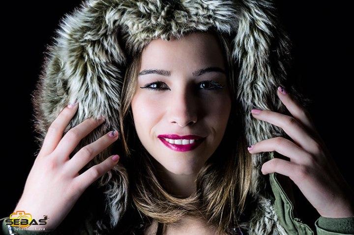 Chica modelo posando con gorro, maquillada y con uñas decoradas con fondo negro