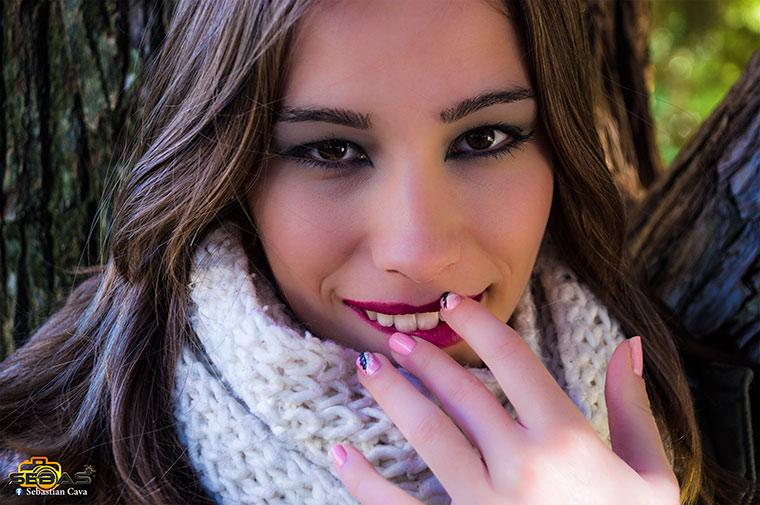 Retrato de chica maquillada con uñas decoradas en bosque y parque