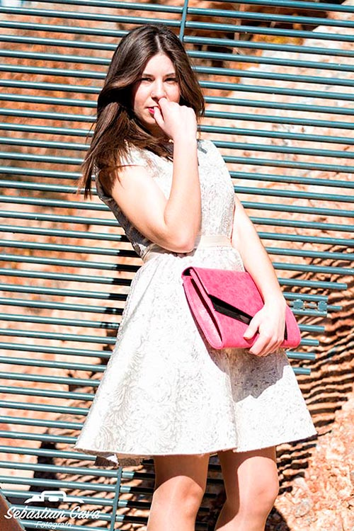 Chica castaña posando con vestido blanco y bolso rosa en verja de metal