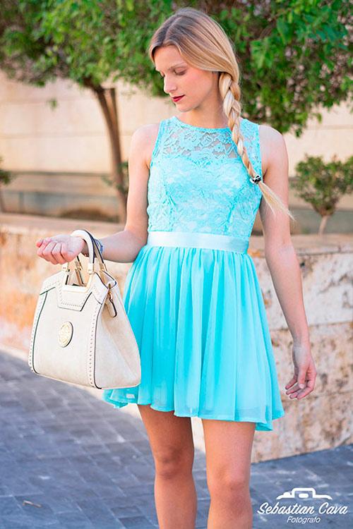 Chica rubia posando con vestido azul y bolsos beige en Alhama de Murcia