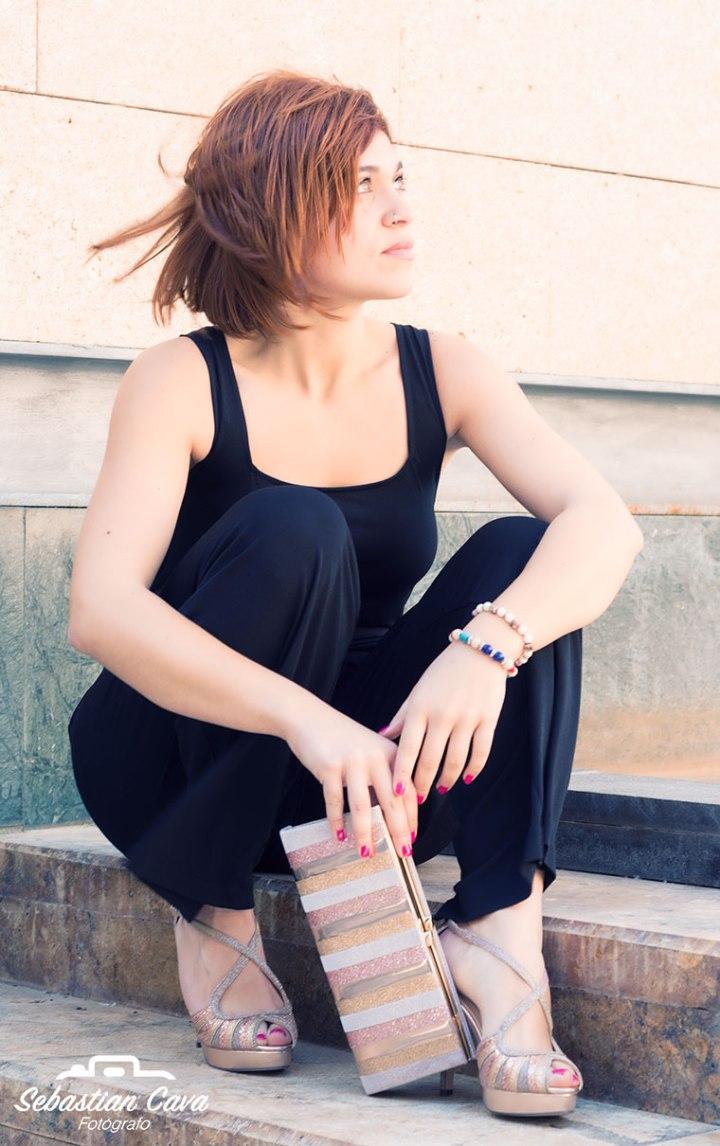Chica con vestido negro y bolso de fiesta