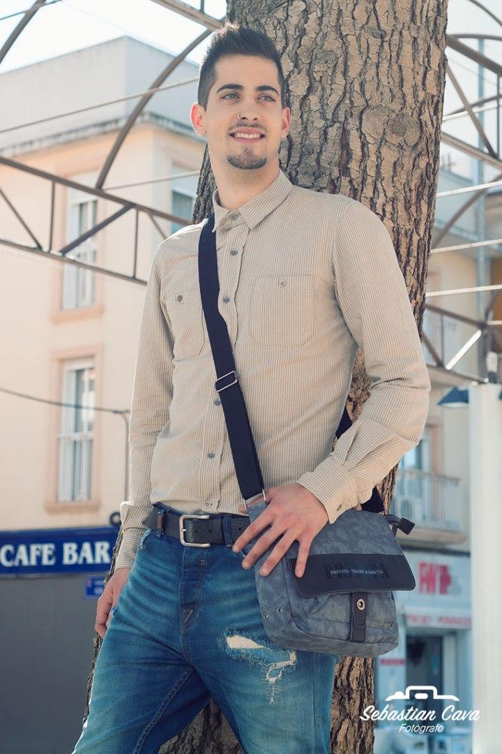 chico modelo con cartera posando en Alhama de Murcia apoyado en arbol
