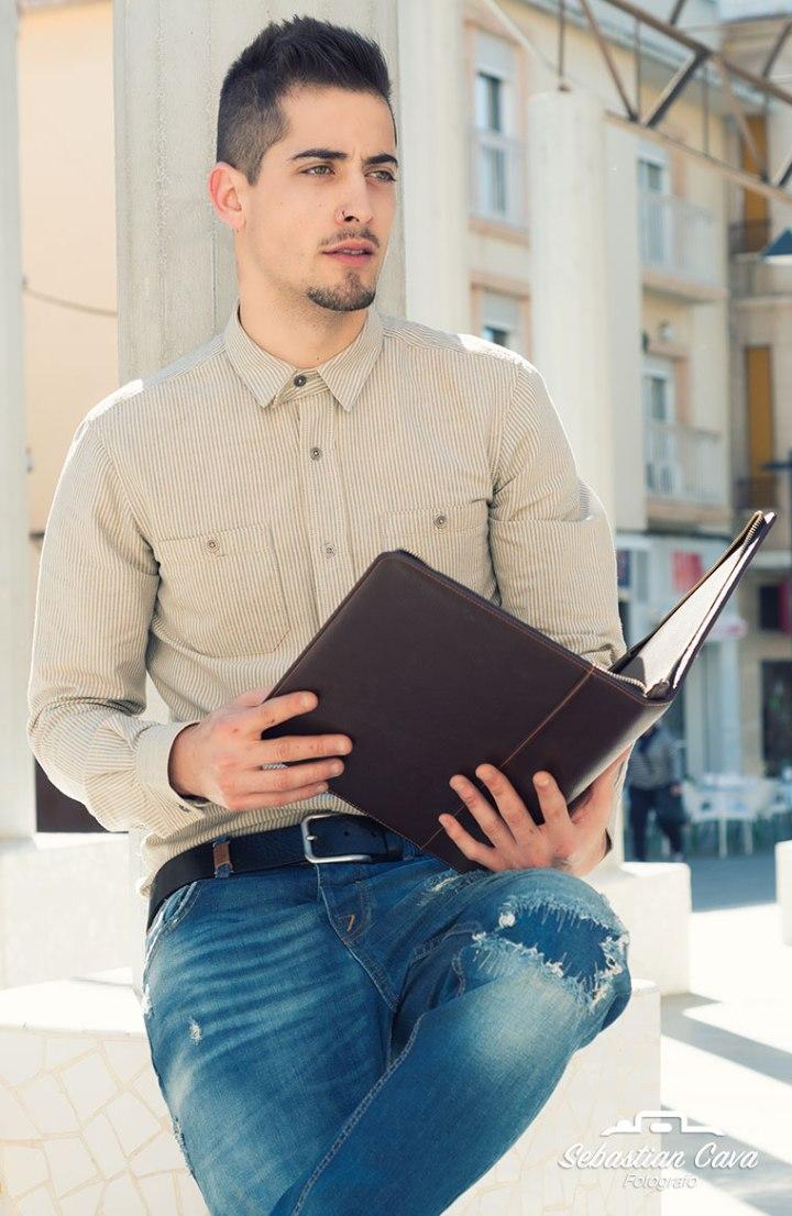 Chico modelo con cartera posando sentado en parque de Alhama de Murcia