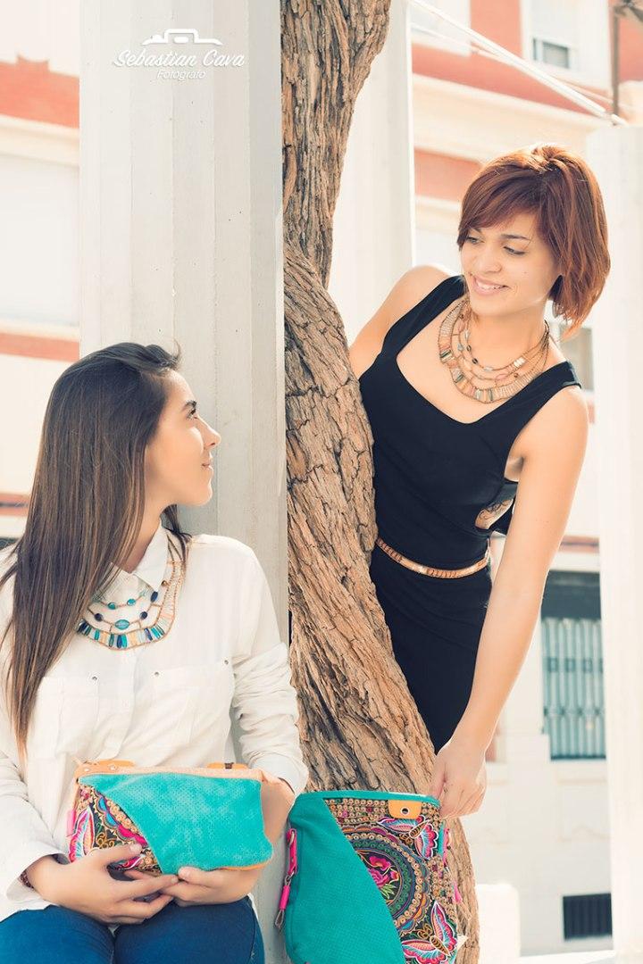 2 chicas posando junto a columna con bolsos coloridos en Alhama de Murcia