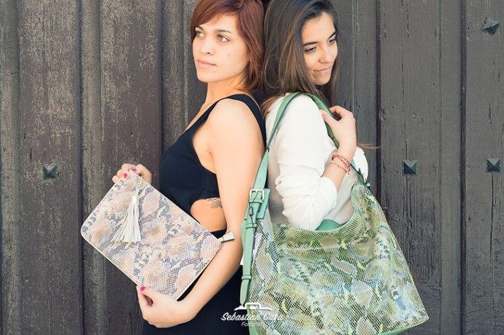 Chicas posando juntas junto a puerta de madera con bolsos de piel de serpiente en Alhama de Murcia