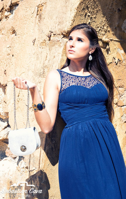 Modelo profesional con vestido azul y bolso blanco apoyada en pared