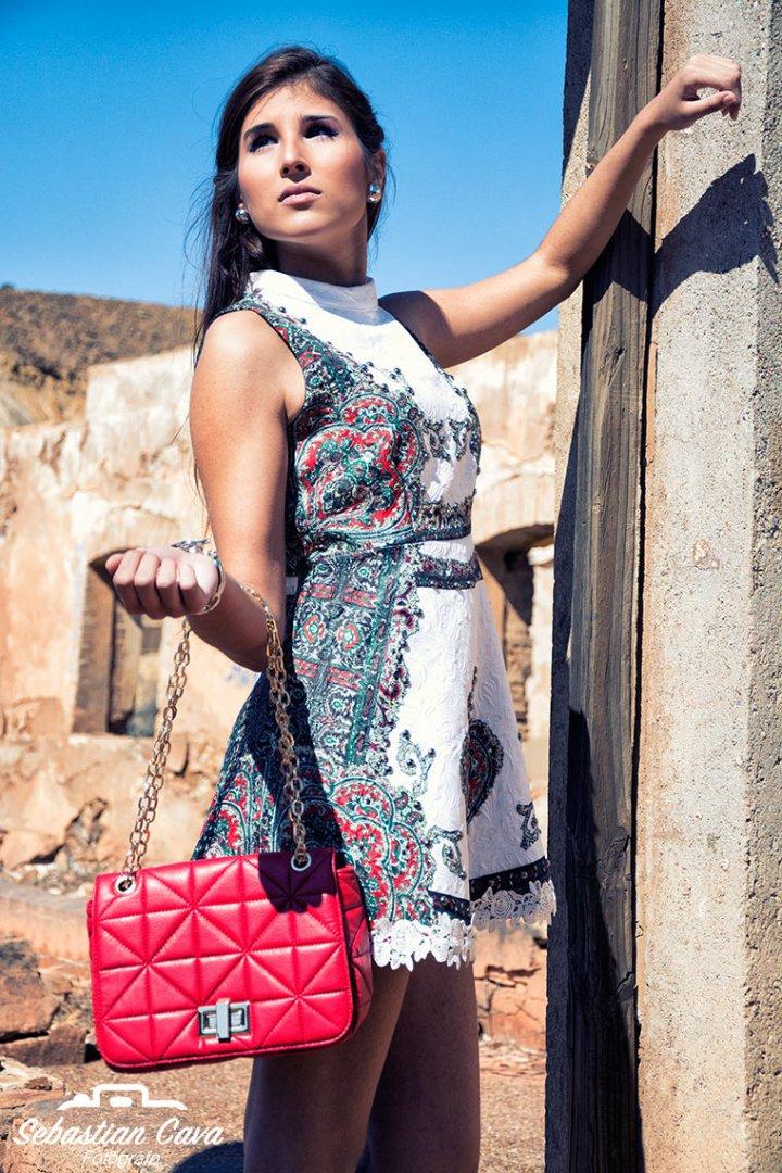 Modelo profesional posando con vestido con flores  y bolso rojo en las minas de mazarron