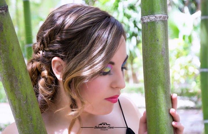 Chica posando entre bambu con peinado de rizos y maquillaje de fiesta