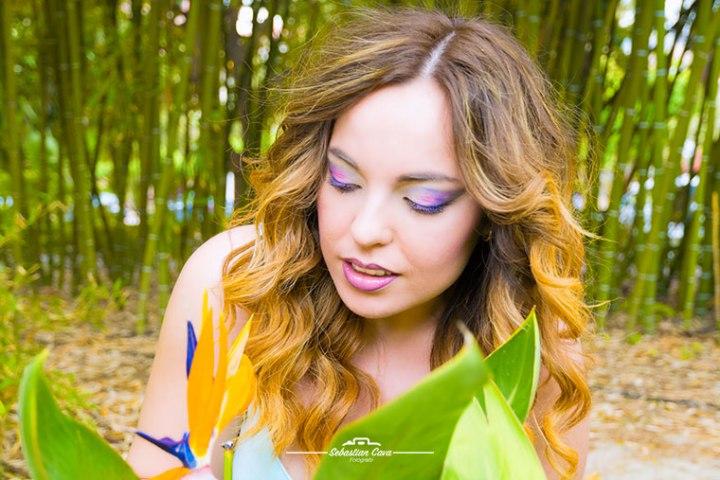 Chica rubia posando delante de una flor con peinado rizos y maquillaje tricolor
