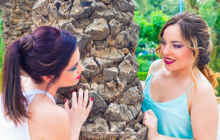 Dos chicas posando junto a palmera mirándose con maquillajes de fiesta y peinados elaborados