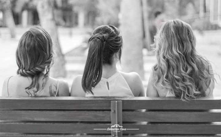 Tres chicas en banco parque con peinados y pelo suelto
