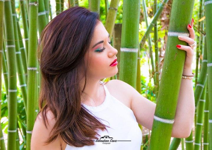 Chica morena posando entre bambu con pelo suelto y paquillaje de fiesta