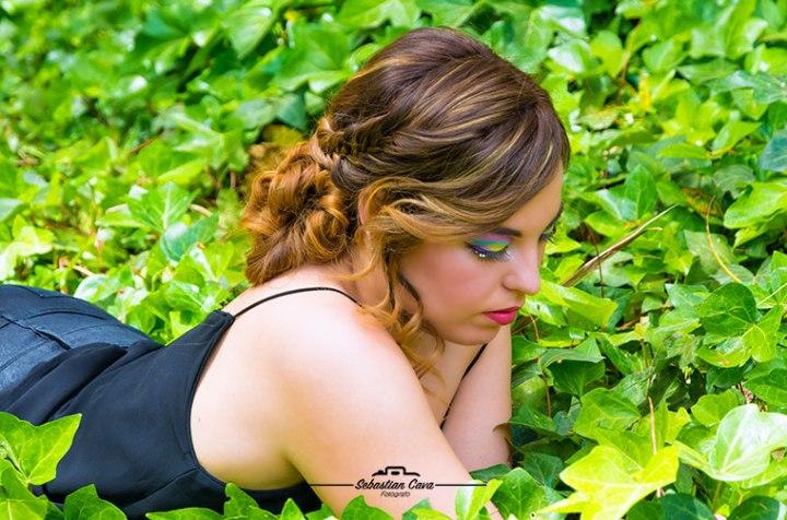 Chica posando tumbada entre yerba verde con peinado rizos y maquillaje de fiesta