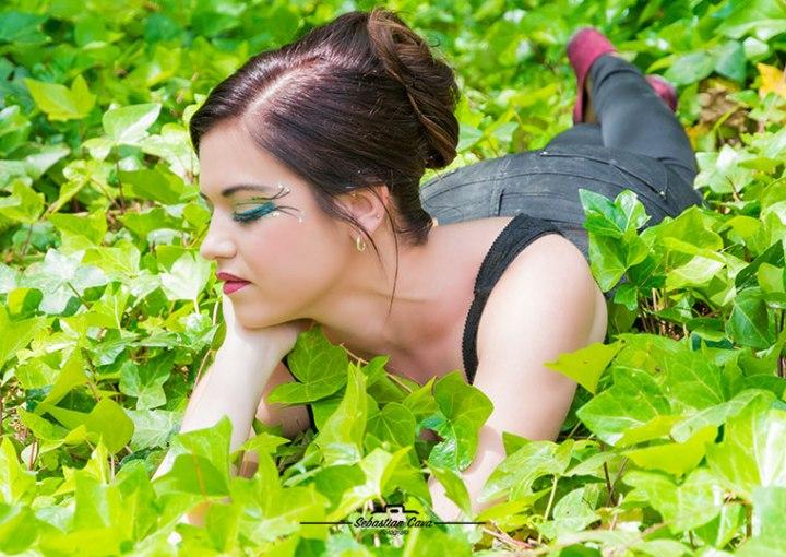 Chica tumbada entre la yerba con moño en el pelo y maquillaje de fantasia Cleopatra