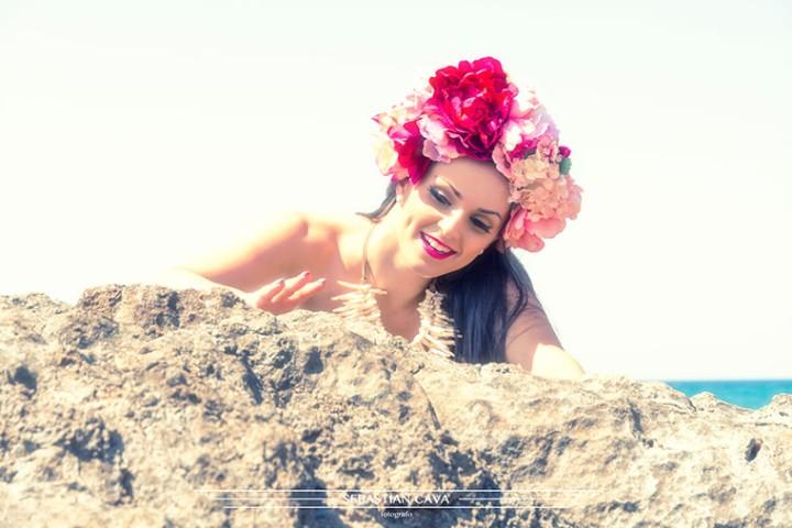 chica entre las rocas con tocado de flores