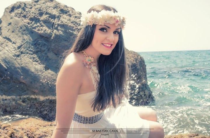 modelo posando junto al mar con corona de flores
