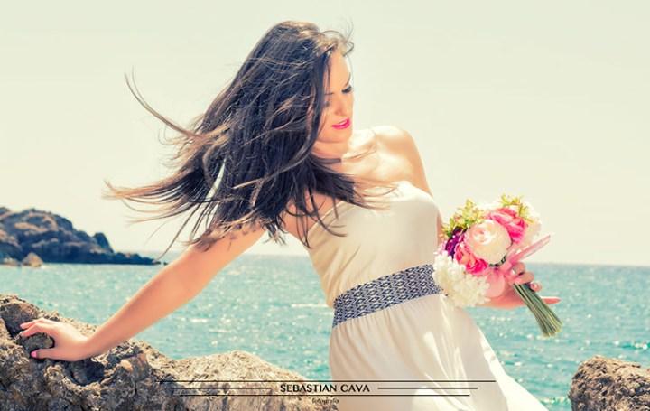 modelo junto al mar con ramo de flores