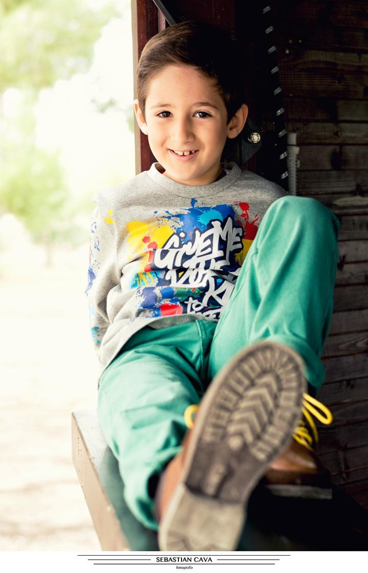 Fotografia niño posando ropa de moda en cabaña