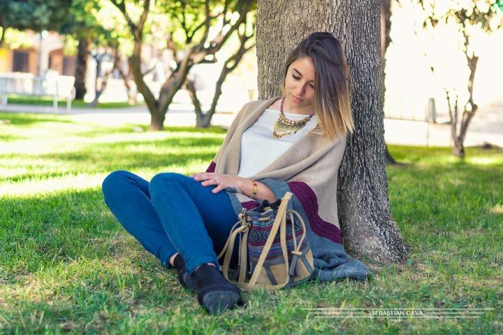 Fotografia chica junto a árbol en parque con bolso moda